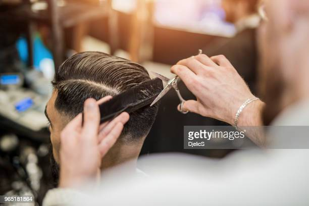 rear view of young man getting a modern haircut. - hairstyle stock pictures, royalty-free photos & images