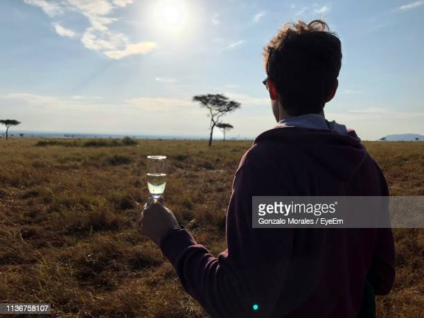 rear view of young man holding champagne flute while standing on land - gonzalo caballero fotografías e imágenes de stock
