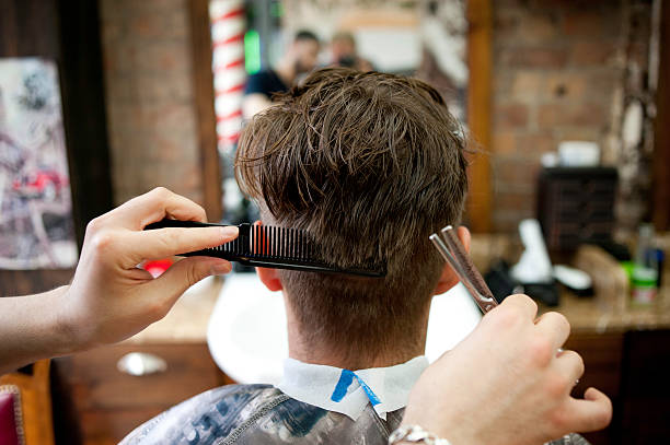 rear view of young man in barbershop having haircut - barber shop stock pictures, royalty-free photos & images