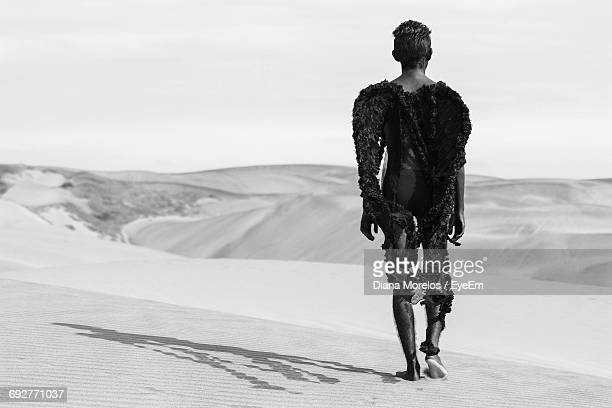 Rear View Of Young Man In Costume Standing At Desert Against Sky