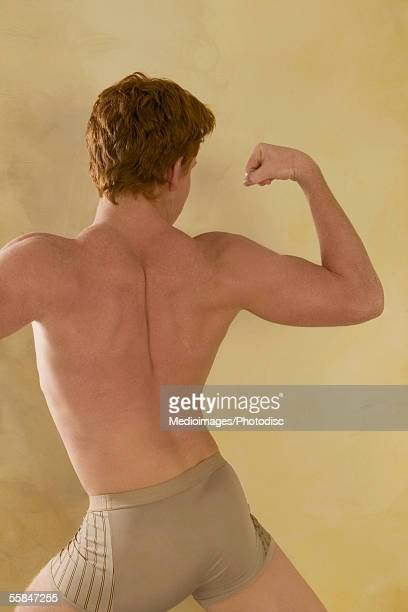 Rear view of young man in underwear doing martial arts