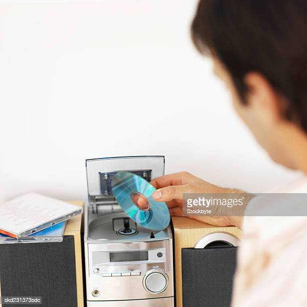 Rear view of young man inserting cd into stereo system