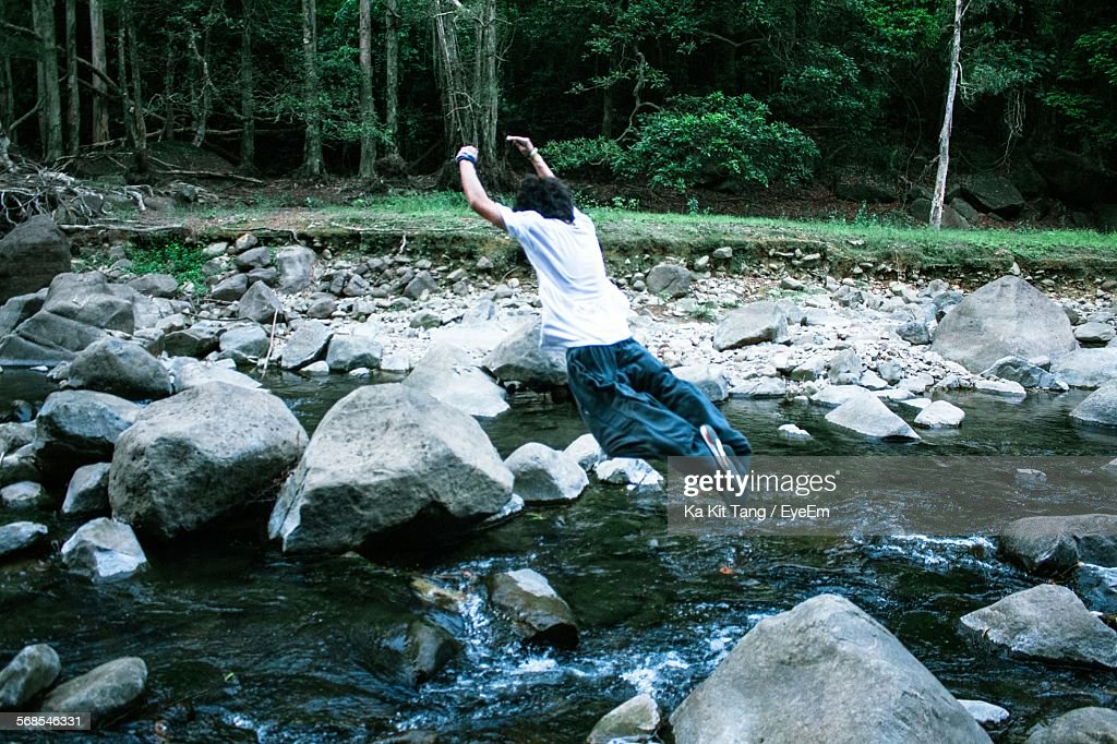 Rear View Of Young Man Jumping In Rocky Stream : Stock Photo