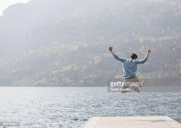 Rear view of young man jumping on pier, Lake Mergozzo, Verbania, Piemonte, Italy