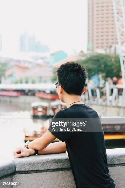 Rear View Of Young Man Leaning On Railing At Clarke Quay