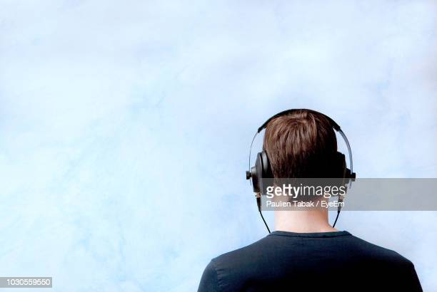 rear view of young man listening music while standing against cloudy sky - paulien tabak stockfoto's en -beelden