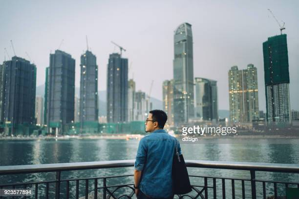 Rear view of young man looking at cityscape by the harbour
