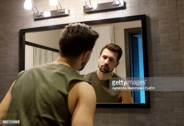 Rear View Of Young Man Looking In Mirror While Standing At Home