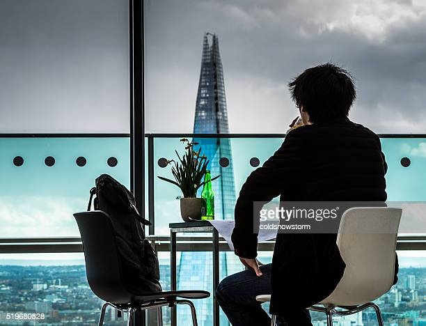 Rear view of Young Man looking out over London Skyline