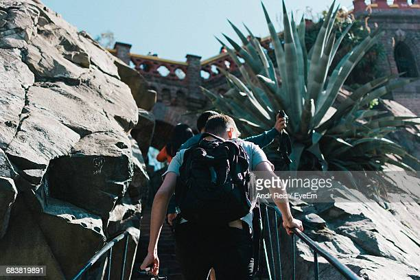 rear view of young man moving on steps amidst rocky mountains - santiago chile stock pictures, royalty-free photos & images