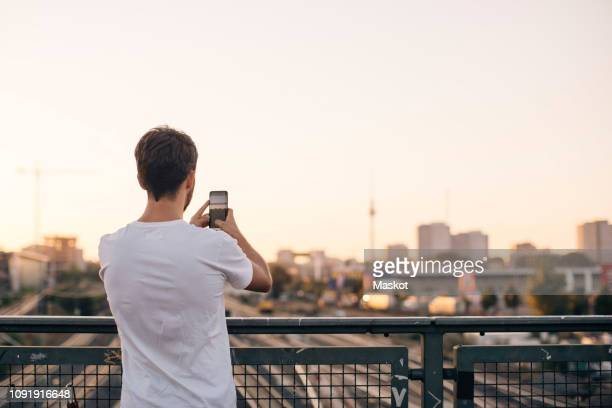 rear view of young man photographing city through mobile phone while standing on bridge against clear sky - vista posterior fotografías e imágenes de stock
