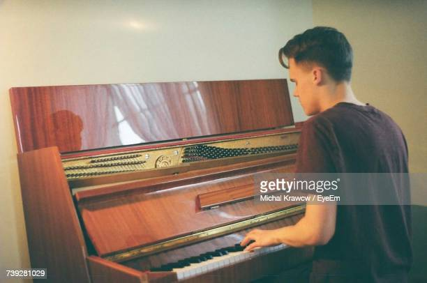 Rear View Of Young Man Playing Grand Piano