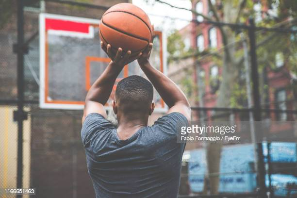 rear view of young man practicing basketball in court - shooting baskets stock pictures, royalty-free photos & images