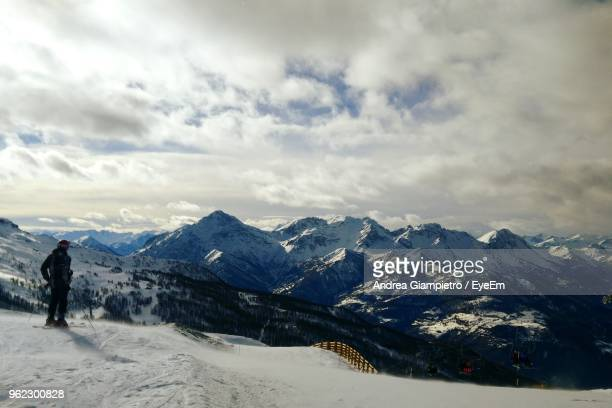 Rear View Of Young Man Skiing On Snowcapped Mountain Against Cloudy Sky