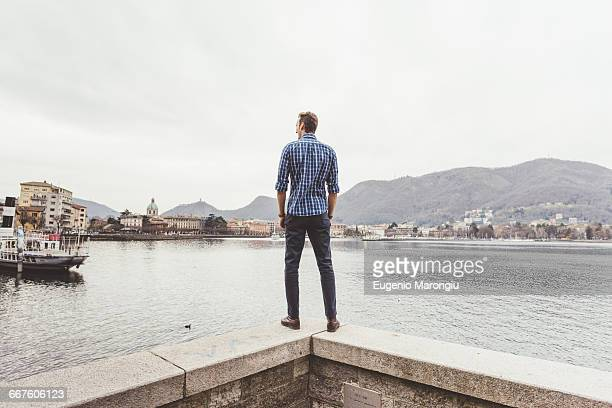 rear view of young man standing on harbour wall looking out, lake como, italy - checked shirt stock photos and pictures