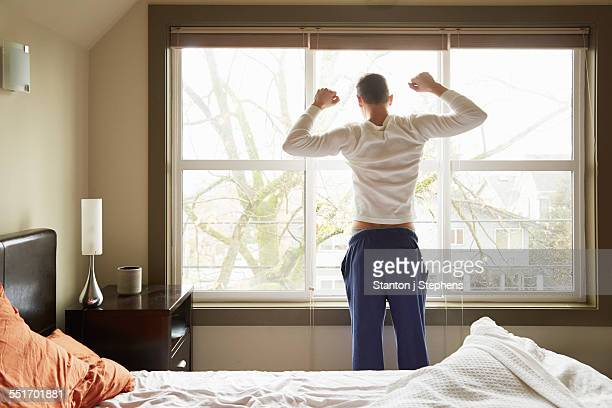 Rear view of young man stretching in front of bedroom window