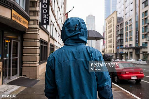 Rear view of young man strolling on rainy street, Seattle, Washington State, USA