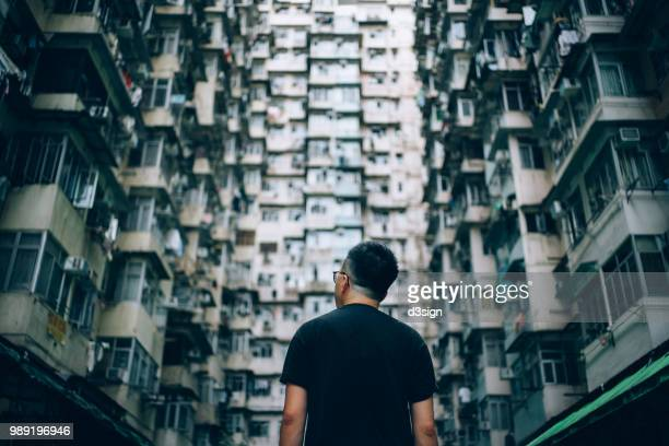 rear view of young man surrounded by old traditional residential buildings and looking up to sky in city - skyscraper film stock pictures, royalty-free photos & images