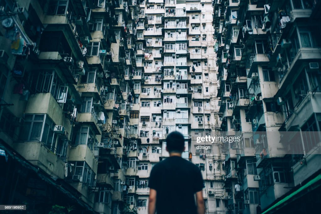 Rear view of young man surrounded by old traditional residential buildings and lost in city : Stock Photo