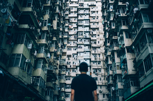 Rear view of young man surrounded by old traditional residential buildings and lost in city - gettyimageskorea