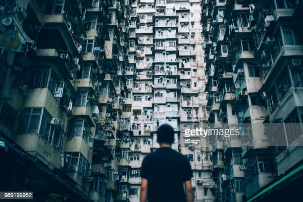 rear view of young man surrounded by old traditional residential buildings and lost in city - skyscraper film stock pictures, royalty-free photos & images