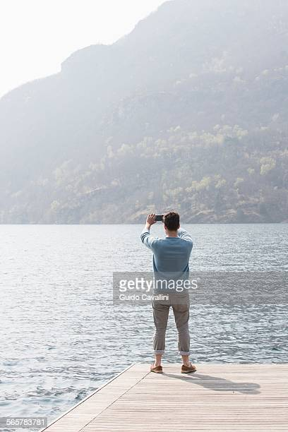 Rear view of young man taking photograph from pier, Lake Mergozzo, Verbania, Piemonte, Italy