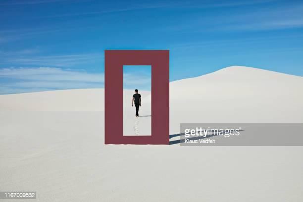 rear view of young man walking at desert seen through door frame - un solo hombre fotografías e imágenes de stock