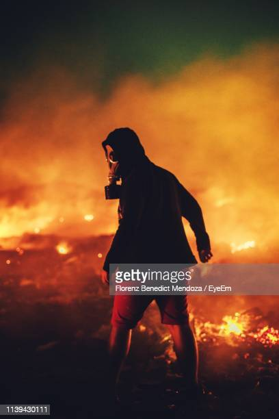 rear view of young man wearing oxygen mask while standing on field against fire at night - in flames i the mask stock pictures, royalty-free photos & images