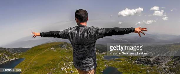 rear view of young man with arms outstretched standing on mountain against sky - krasimir georgiev stock photos and pictures