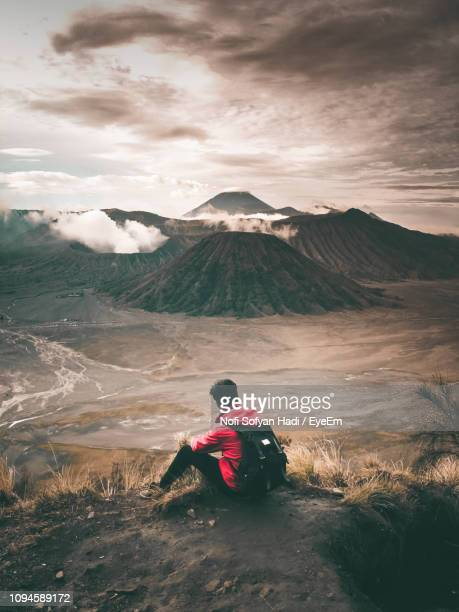 Rear View Of Young Man With Backpack Sitting On Mountain Against Cloudy Sky