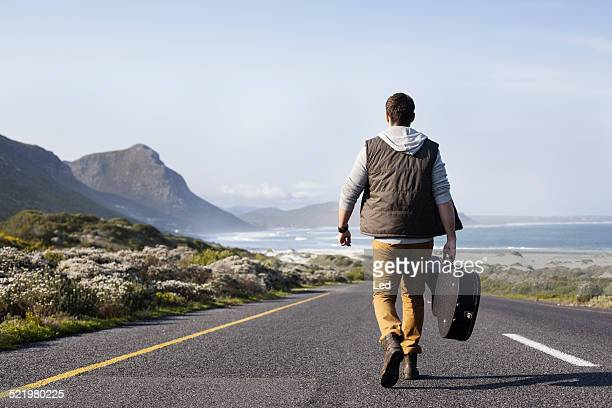 rear view of young man with guitar case walking on coastal road, cape town, western cape, south africa - guitar case stock pictures, royalty-free photos & images