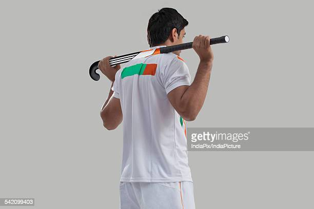 Rear view of young man with hockey stick isolated over gray background