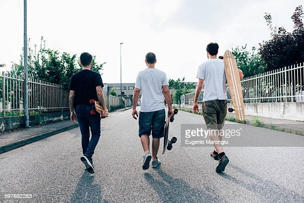 Rear view of young men walking on path carrying skateboards