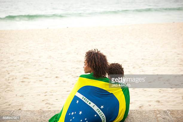 Rear view of young mother and son wrapped in Brazilian flag looking out from Ipanema beach, Rio De Janeiro, Brazil