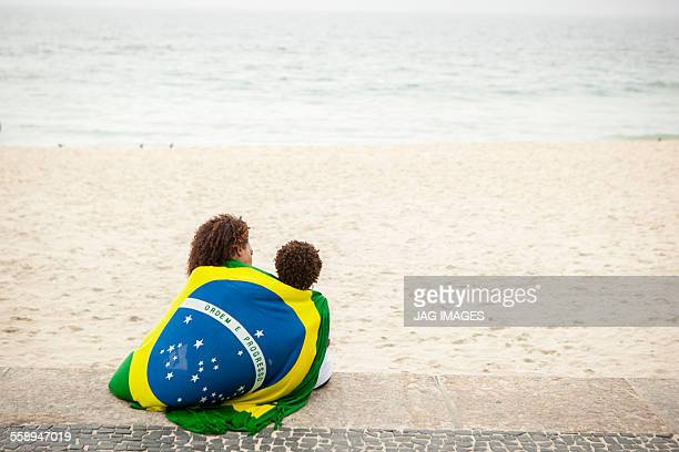 Rear view of young mother and son wrapped in Brazilian flag on Ipanema beach, Rio De Janeiro, Brazil