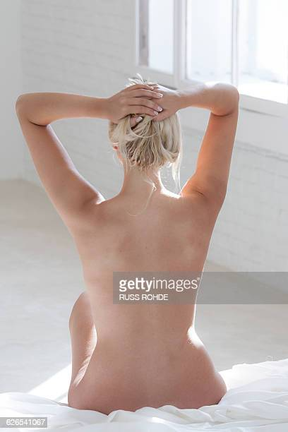 Rear view of young naked woman sitting on bed with hands in blond hair
