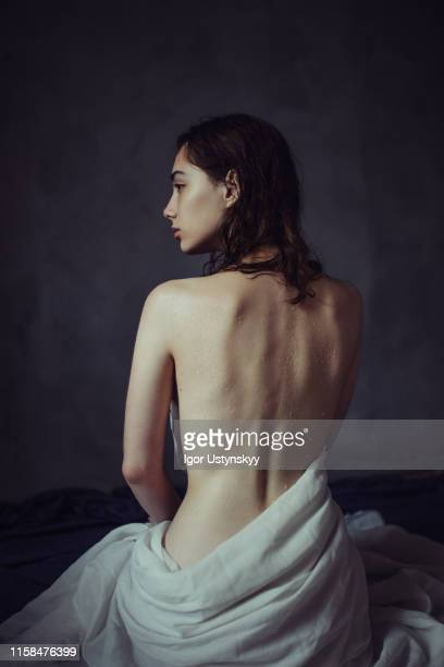 rear view of young nude woman sitting on floor - donna schiena nuda foto e immagini stock