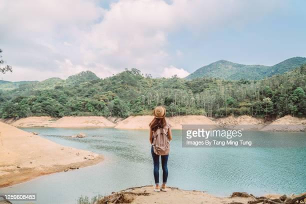 rear view of young pretty woman enjoying a scenic beautiful lake view joyfully while she is hiking on nature trail - paisajes de hongkong fotografías e imágenes de stock
