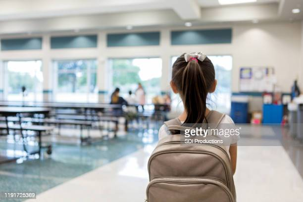 rear view of young schoolgirl entering cafeteria - ponytail stock pictures, royalty-free photos & images
