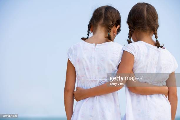 Rear view of young sisters wearing matching dresses and hugging outdoors
