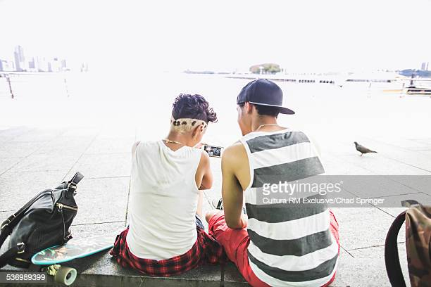 Rear view of young skateboarding couple looking  at smartphone