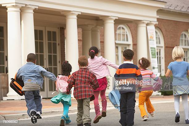 rear view of young students running to building - preschool building stock pictures, royalty-free photos & images