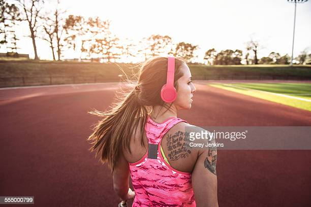 Rear view of young tattooed female athlete running on race track