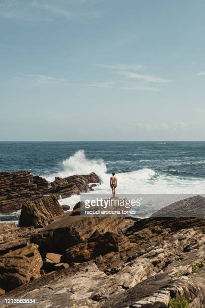 rear view of young white man in swimsuit stand up on the rocks by the sea - オンダリビア ストックフォトと画像