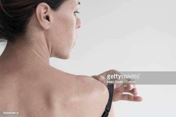 Rear View Of Young Woman Adjusting Bra Against White Background