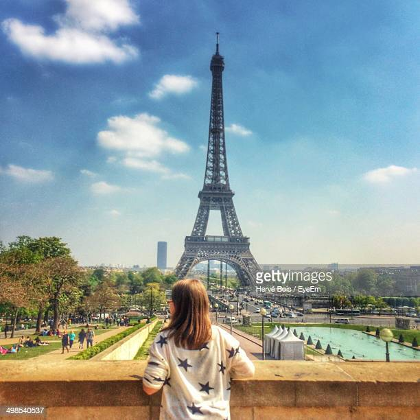 Rear view of young woman against Eiffel Tower