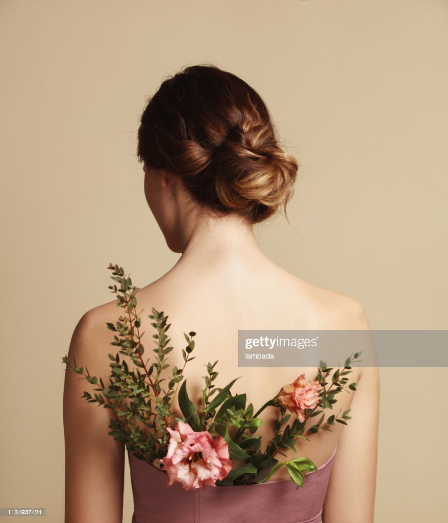 Rear view of young woman and flowers : Stock Photo