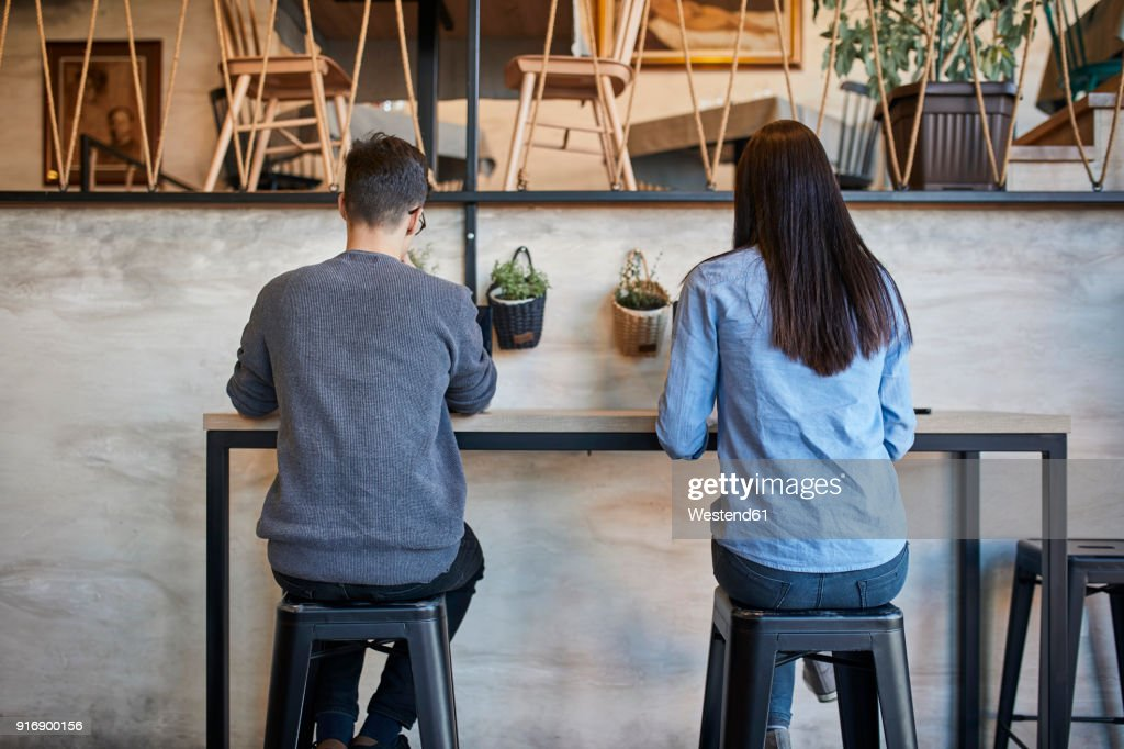 Rear view of young woman and man sitting in a cafe : Stock Photo