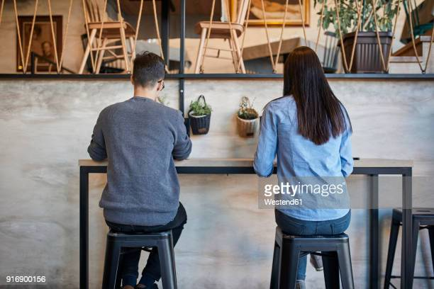 rear view of young woman and man sitting in a cafe - sitting foto e immagini stock