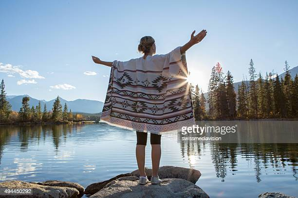 Rear view of young woman arms outstretched by the lake